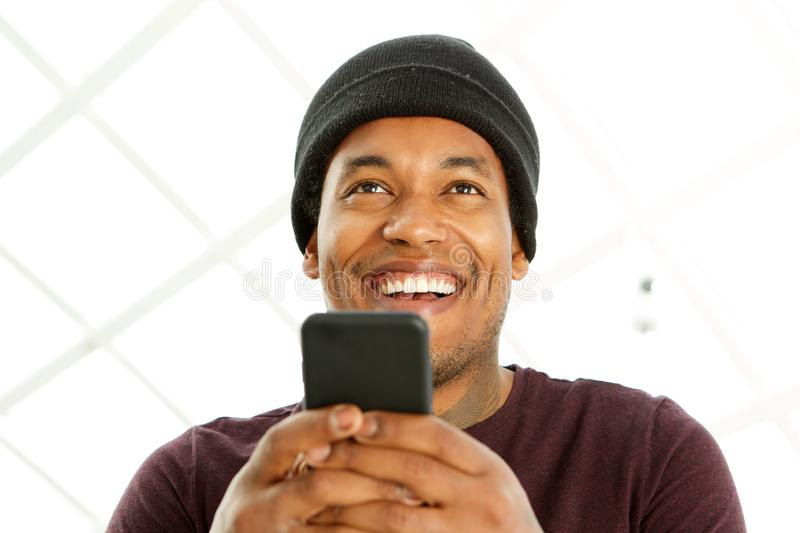 Close up handsome african american man smiling and holding cellphone royalty free stock image