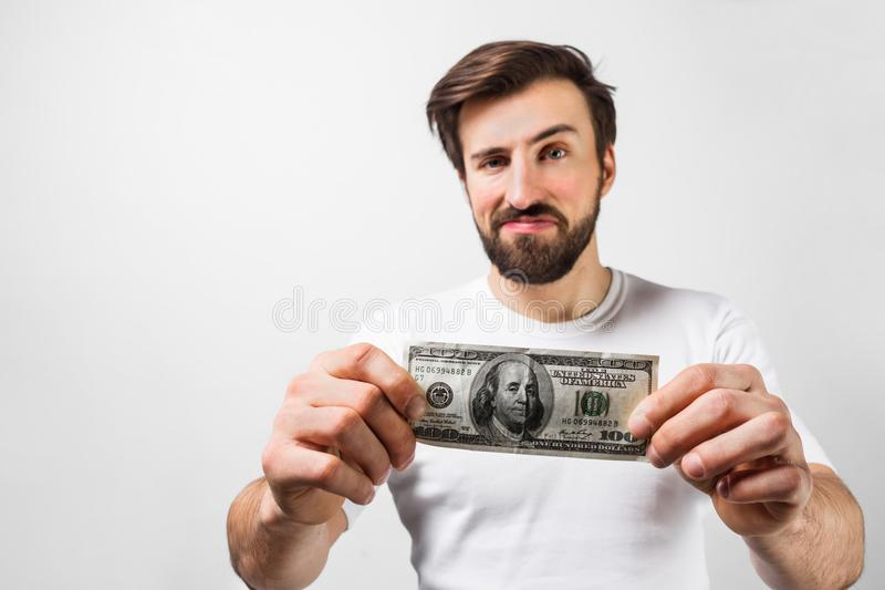 Close up of handsome brunette man standing near the white wall and holding a dollar bill. He is showing that he has one stock photos