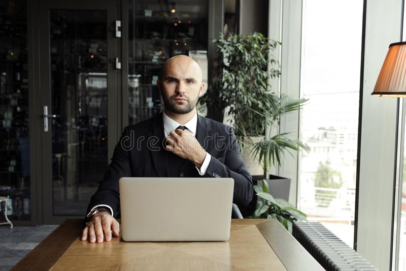 Close up of handsome businessman, working on laptop in restaurant royalty free stock photos