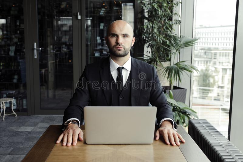 Close up of handsome businessman, working on laptop in restaurant royalty free stock photo