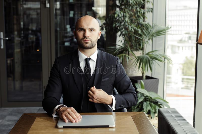 Close up of handsome businessman, working on laptop in restaurant stock images