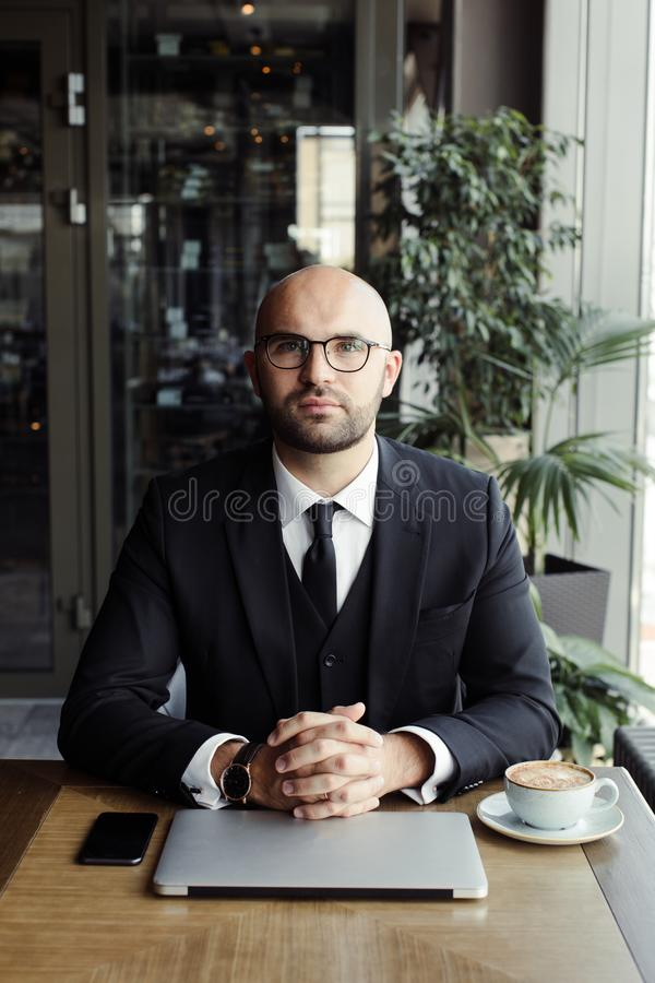 Close up of handsome businessman, working on laptop in restaurant royalty free stock images