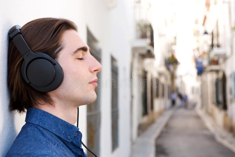 Close up handsome meditative man with headphones on city street royalty free stock photography