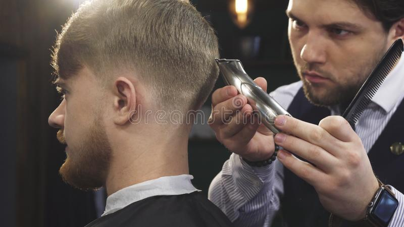 Close up of a handsome professioanl barber stylign hair of a man. Cropped close up of a handsome professional barber working at his barbership using electrical royalty free stock image