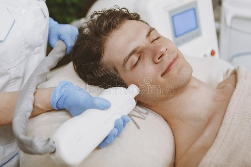 Handsome man getting facial skincare treatment stock photos