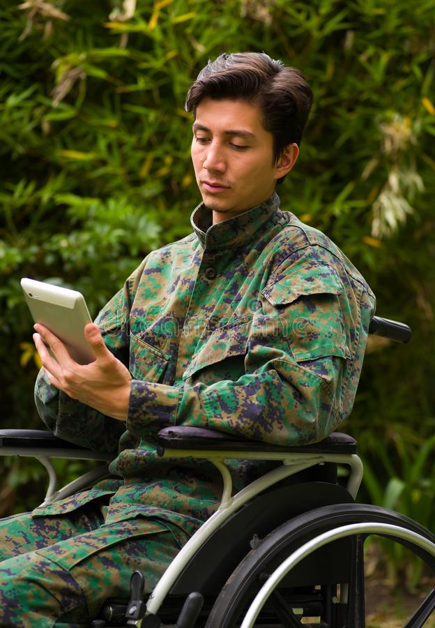 Close up of a handsome soldier sitting on wheel chair using his tablet with both hands, and wearing military uniform in. A nature background royalty free stock photography