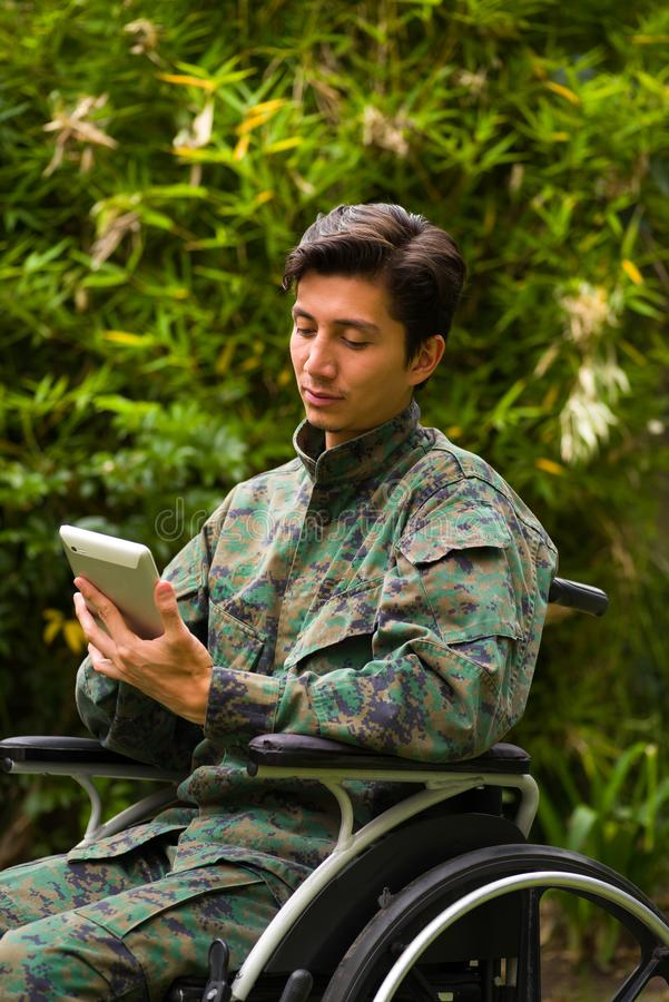 Close up of a handsome soldier sitting on wheel chair using his tablet with both hands, and wearing military uniform in. A nature background stock image