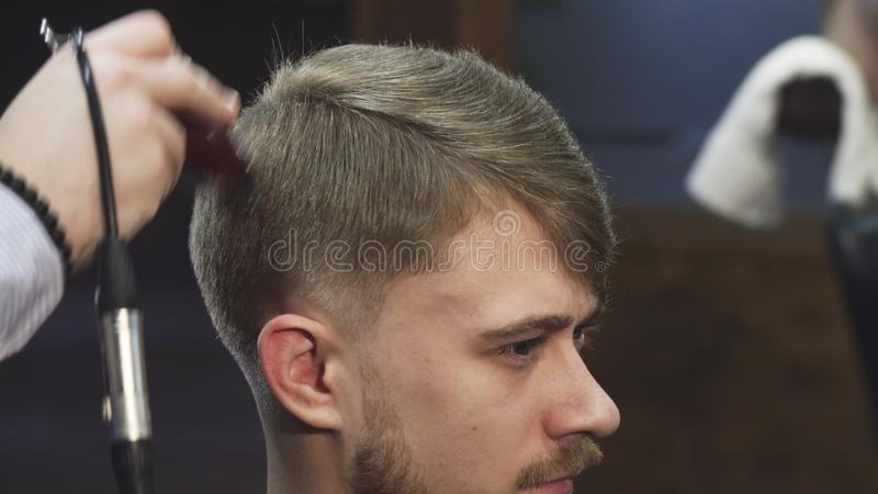 Close up of a handsome yougn man getting a haircut at the barbershop. Cropped sliding close up of a young handsome men smiling while professional barber trimming stock photography