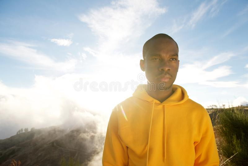 Close up handsome young african american man in hoodie standing outside with sunny background royalty free stock photos
