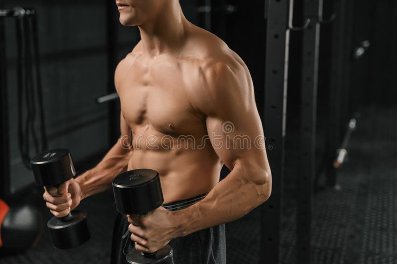 Close-up of a handsome young man lifting dumbbell. Fitness muscular body on dark background. Crossfit training royalty free stock photography