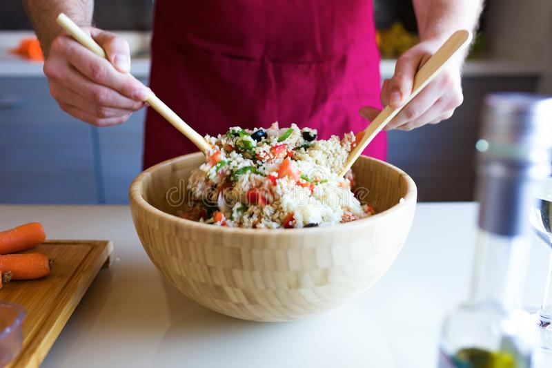 Handsome young man preparing quinoa salad with vegetables in the kitchen. stock image