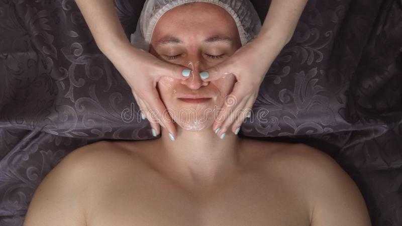 Close up of a handsome young man receiving facial massage at spa center stock images