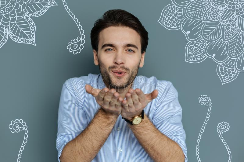 Close up of handsome young man sending air kiss to you stock photo