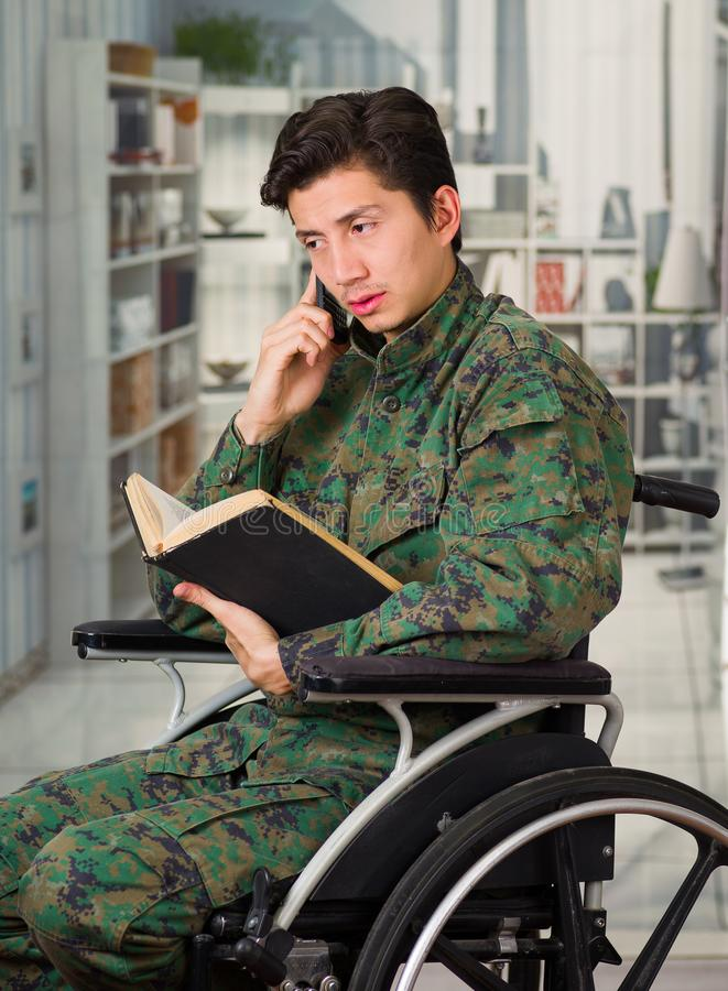 Close up of a handsome young soldier sitting on wheel chair reading a book at home and using his cellphone in a blurred. Background stock photos