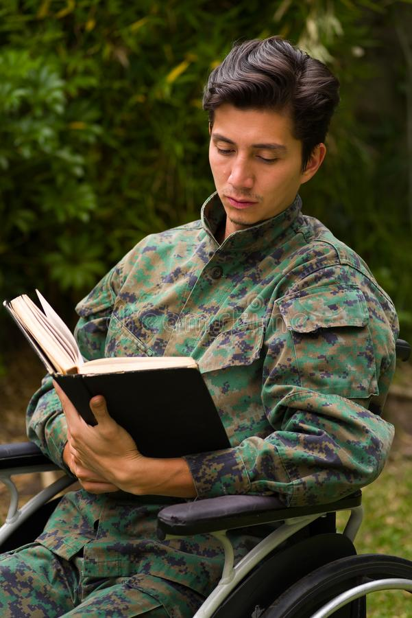 Close up of a handsome young soldier sitting on wheel chair reading a book in the patio, in a backyard background.  royalty free stock photography