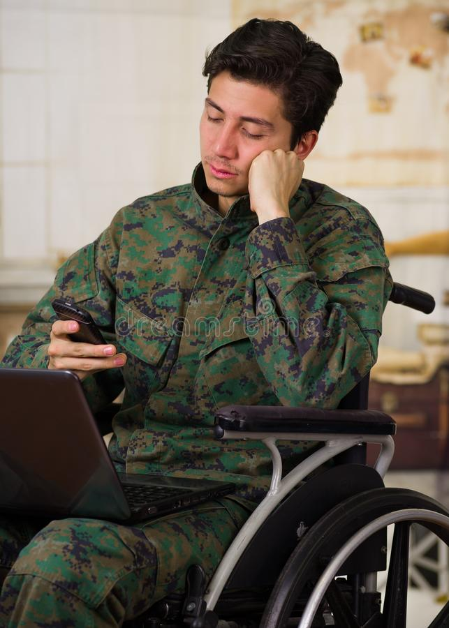 Close up of a handsome young soldier sitting on wheel chair using his cellphone while his computer is over his legs. Wearing military uniform in a blurred stock photos
