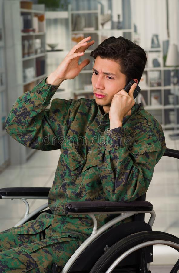 Close up of a handsome young soldier sitting on wheel chair using his cellphone, wearing military uniform in a blurred. Background stock photos