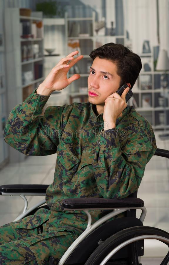 Close up of a handsome young soldier sitting on wheel chair using his cellphone, wearing military uniform in a blurred. Background royalty free stock image