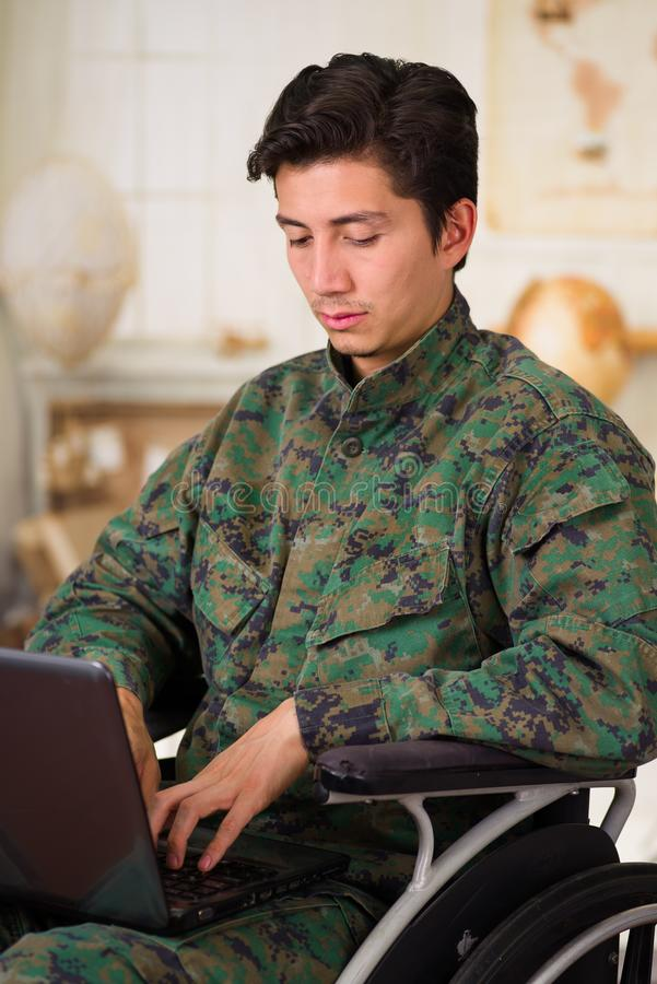 Close up of a handsome young soldier sitting on wheel chair using his computer over his legs, wearing military uniform. In a blurred background royalty free stock image
