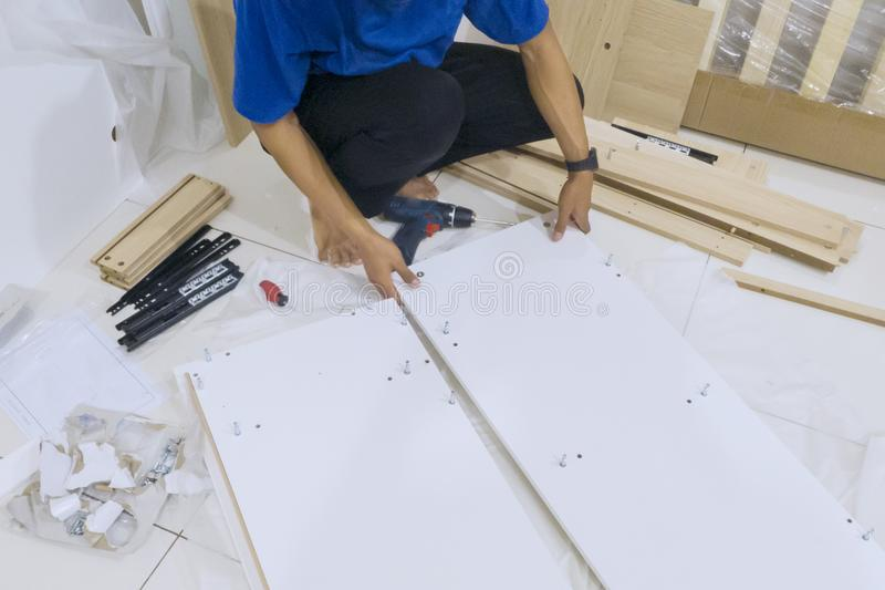 Handyman assembling parts of a piece of furniture royalty free stock photo
