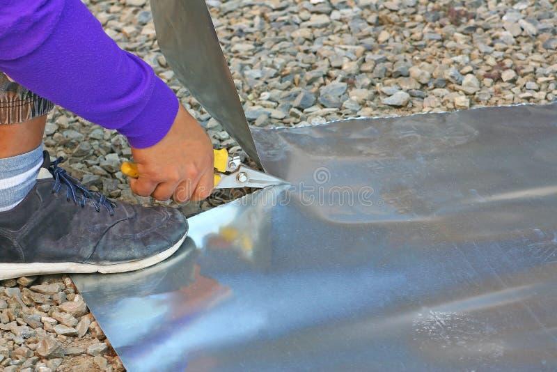 Handyman cutting galvanized steel sheet stock photo