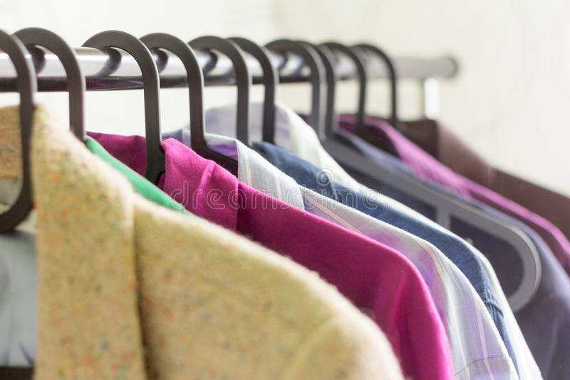 Close - up hangers with different clothes.Shirts and jackets of different colors hanging on a hanger stock image