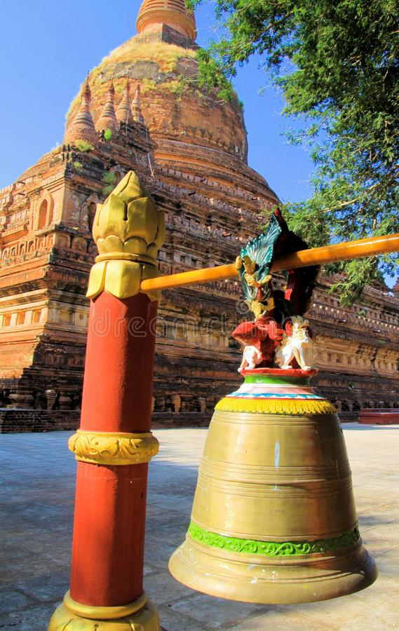 Close up of hanging bell with ancient pagoda in background -  Bagan, Myanmar royalty free stock photography