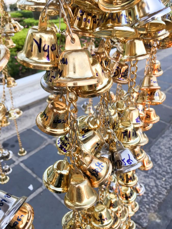 Close up hanging small gold bells for luck in Wat Chaeng , Bangkok , Thailand stock photography
