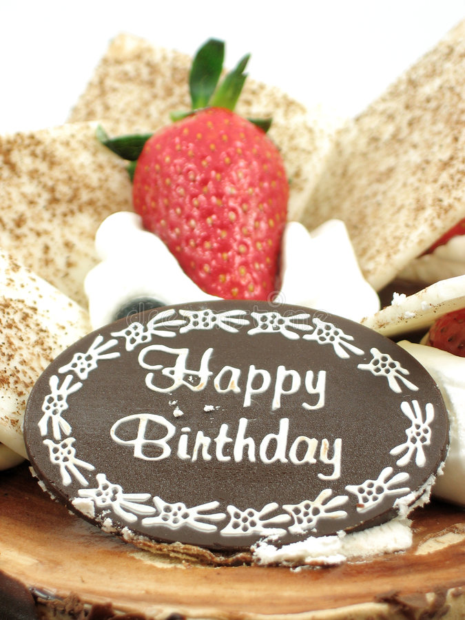 Close up of Happy birthday!. Close up of Happy Birthday and a strawberry topped on a chocolate birthday cake royalty free stock photography