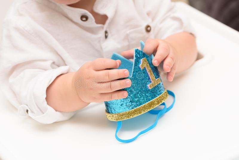 Close up on happy birthday baby boy hand with blue crown with digit one. royalty free stock photos
