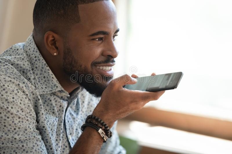 Close up happy black man dictating voice message. Close up happy smiling millennial african american man holding smartphone, dictating voice message, recording stock images