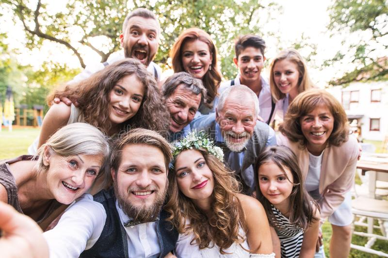 Bride, groom with guests taking selfie at wedding reception outside in the backyard. royalty free stock image