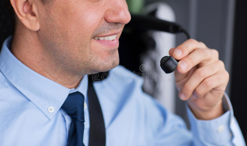 Close up of happy bus driver talking to microphone. Transport, tourism, road trip and people concept - close up of happy bus driver talking to microphone stock photos