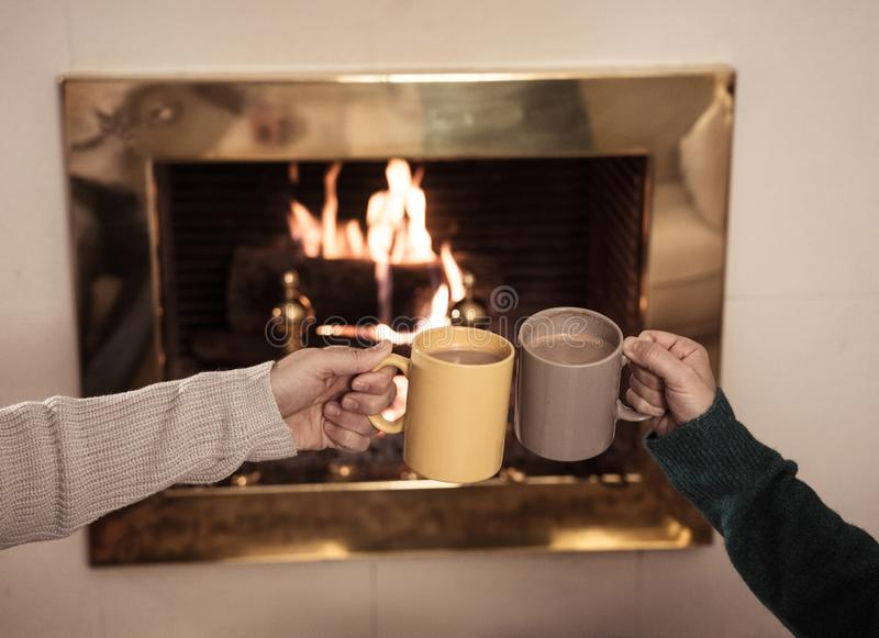 Close up of happy couple drinking hot drink by fire place celebrating love and winter holidays vacation stock image
