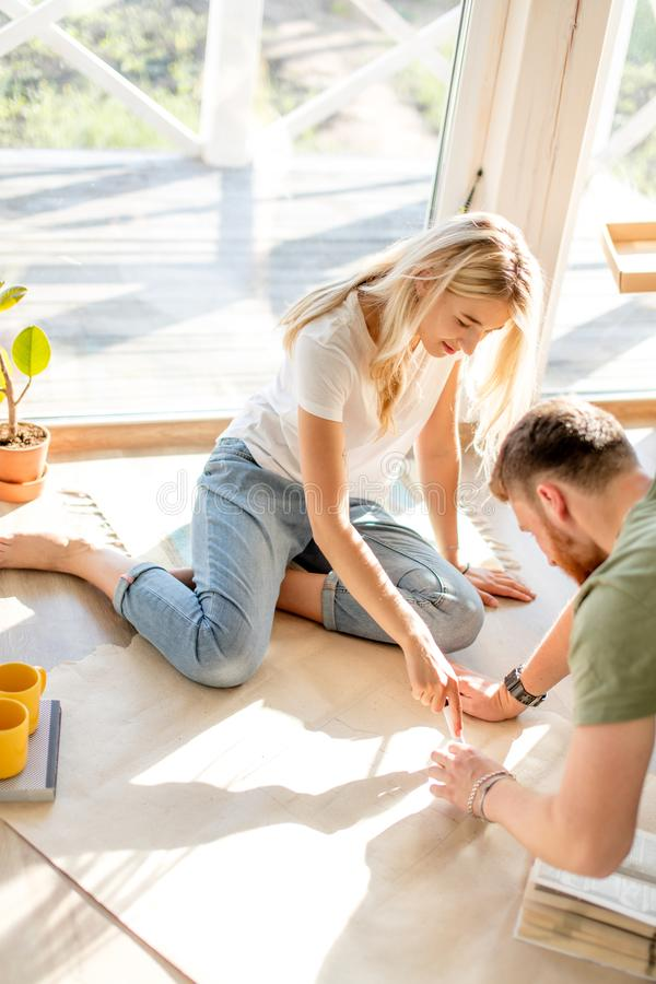 Couple looking blueprints of they new house. Planning interior design royalty free stock image