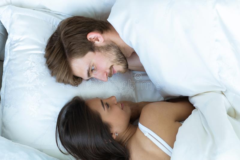 Close-up of happy couple is lying in bed together. Enjoying the company of each other. royalty free stock photos