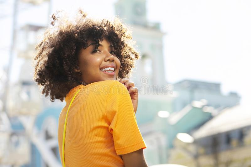 Close up of a happy curly-haired girl smiling during sightseeing stock photos