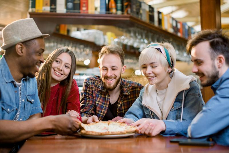 Close up happy diverse friends eating pizza in cafe together, biting slices, multiracial people enjoying Italian junk stock photography