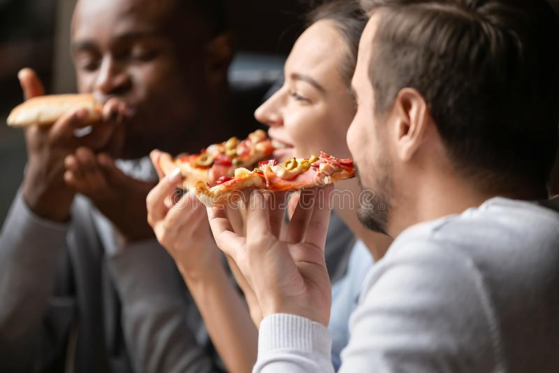 Close up happy diverse friends eating pizza in cafe together stock photo