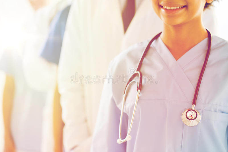 Close up of happy doctor or nurse with stethoscope stock photos