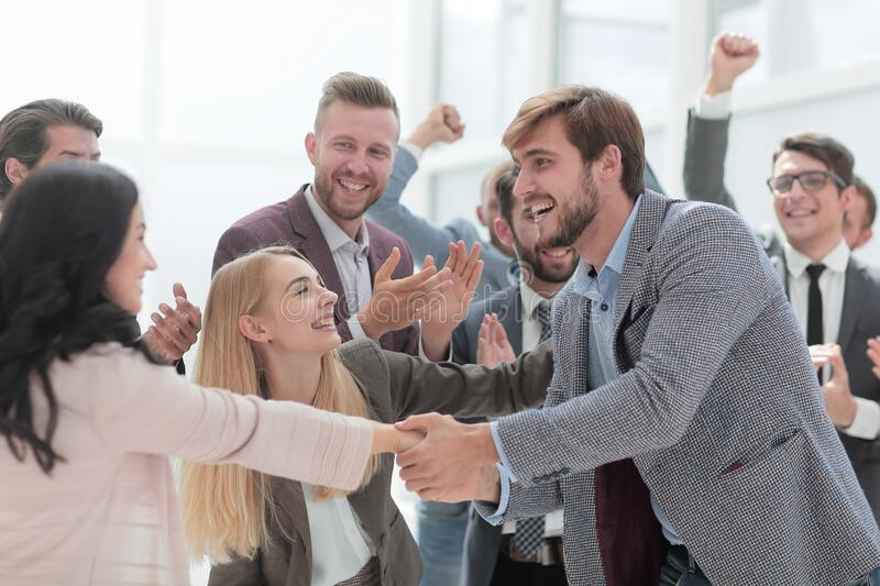 Happy employees congratulating each other on the victory. royalty free stock photo