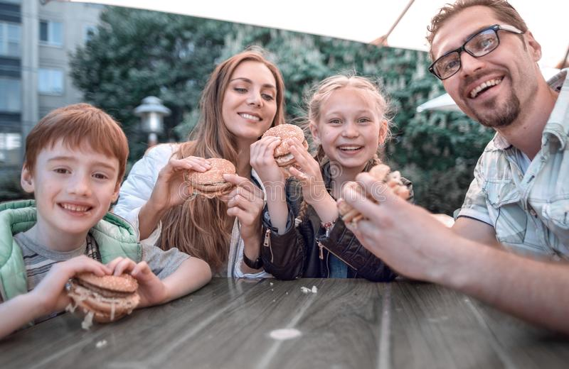 Close up. happy family with hamburgers, sitting at a table. In a fast food restaurant, outdoors royalty free stock photography