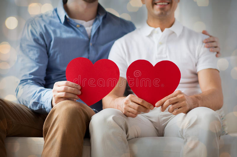 Close up of happy gay male couple with red hearts. People, homosexuality, same-sex marriage, valentines day and love concept - close up of happy gay male couple stock photo