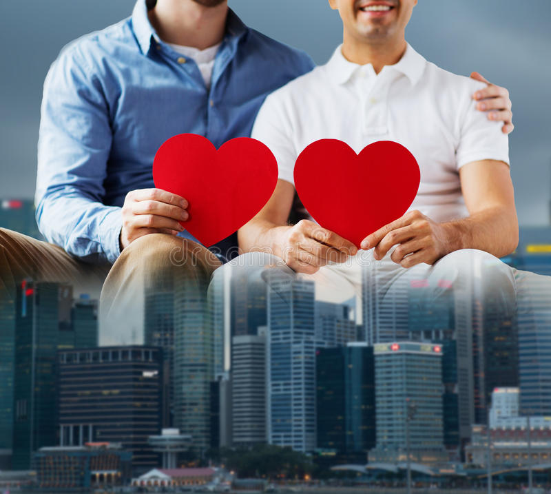 Close up of happy gay male couple with red hearts. People, homosexuality, same-sex marriage, valentines day and love concept - close up of happy gay male couple stock image
