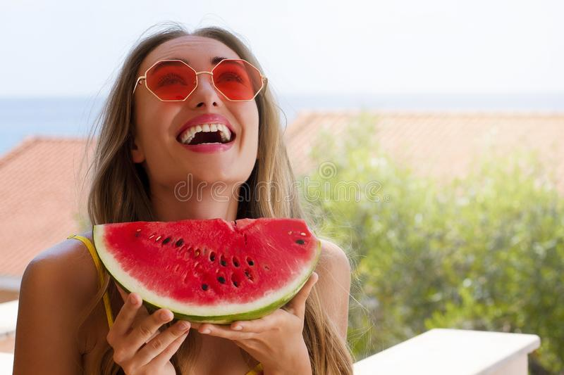 Close Up Of Happy Girl in pink sunglasses and watermelon fruit. Summer holidays and fun time weekend. Summertime concept. Smiling. Close Up Of Happy Girl in pink stock photography