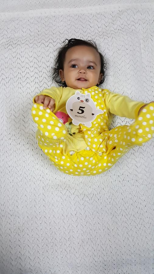 Beautiful Infant playing with 5 month tag stock photography