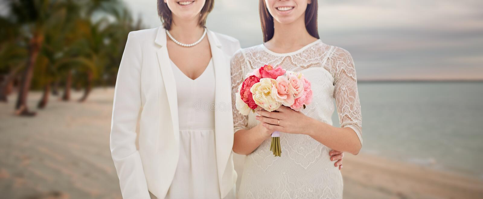 Close up of happy lesbian couple with flowers. People, homosexuality, same-sex marriage, honeymoon and love concept - close up of happy married lesbian couple royalty free stock photo
