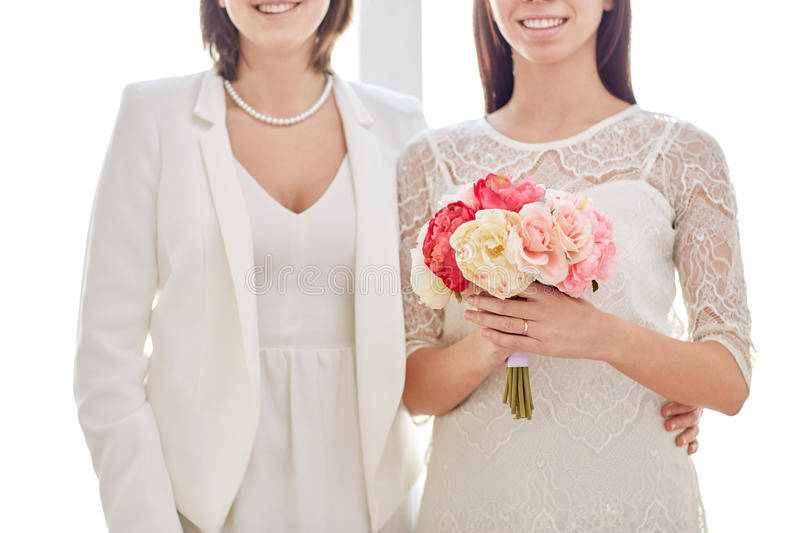 Close up of happy lesbian couple with flowers stock image