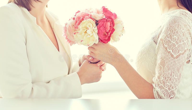 Close up of happy lesbian couple with flowers. People, homosexuality, same-sex marriage and love concept - close up of happy married lesbian couple with flower royalty free stock photos