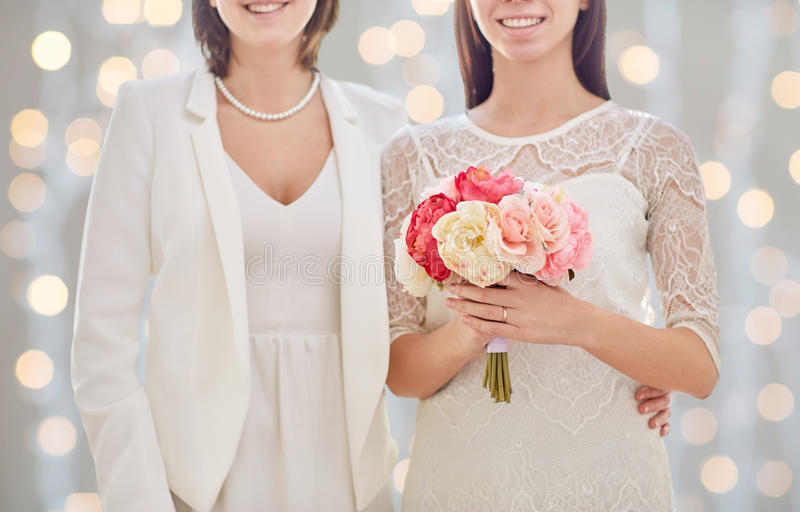 Close up of happy lesbian couple with flowers. People, homosexuality, same-sex marriage and love concept - close up of happy married lesbian couple with flower stock image